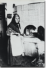 Tom's Great-Great-Great Grandmother baking bread outside in a brick oven in Sicily, 1872.